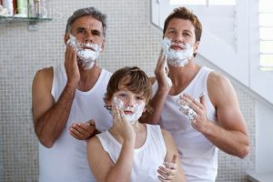 grandfather, father and son applying shaving cream --- Image by © Ole Graf/Corbis